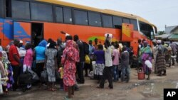 FILE - People board a commercial bus to flee after attacks by Boko Haram in Bama and other parts of Maiduguri, Nigeria, Sept. 8, 2014.