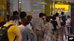 People queue up outside the DHL Express store in Hong Kong, Monday, June 1, 2020. Throngs of people lined up at DHL courier outlets across the city on Monday, many to send documents to the U.K. to apply for or renew what is known as a British…