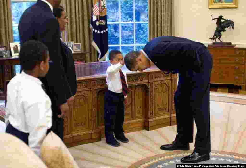 Un employé qui part à la retraite a demandé une photo souvenir avec le président. Son fils a questionné Obama sur ses cheveux puis les a touchés pour voir si c'était comme les siens, le 8 mai 2009. (White House/Pete Souza)