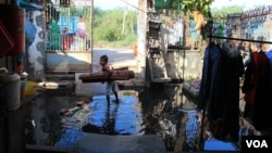 A girl stands in a flood of water, holding a sleeping mat, in front of Khoeun Sovat's house in Boeung Kak community in Phnom Penh, Cambodia, Nov. 13, 2014. (Nov Povleakhena/VOA Khmer)
