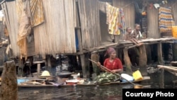 FILE - A woman paddles a canoe around a Lagos waterfront neighborhood on her daily trip to sell bean cakes to residents, July 24, 2012.