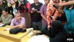 Suratmi (kanan, mengenakan baju warna hitam yang juga menutup wajahnya), istri terduga teroris Siyono yang tewas ketika diperiksa Densus 88 Selasa (29/3) menyerahkan 2 bungkusan uang kepada Busyro Muqodas Ketua PP Muhammadiyah Bidang hukum dan HAM. (VOA/