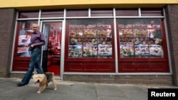 Kevin Maguire walks his dog past a vacant shop, with graphics pasted to the outside to make it look like a working butcher's shop, in the village of Belcoo, Northern Ireland, June 3, 2013.