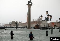 Ljudi hodaju potopljenim Trgom svetog Marka, tokom perioda visokih voda u Veneciji, Italija, 29. oktobra 2018.