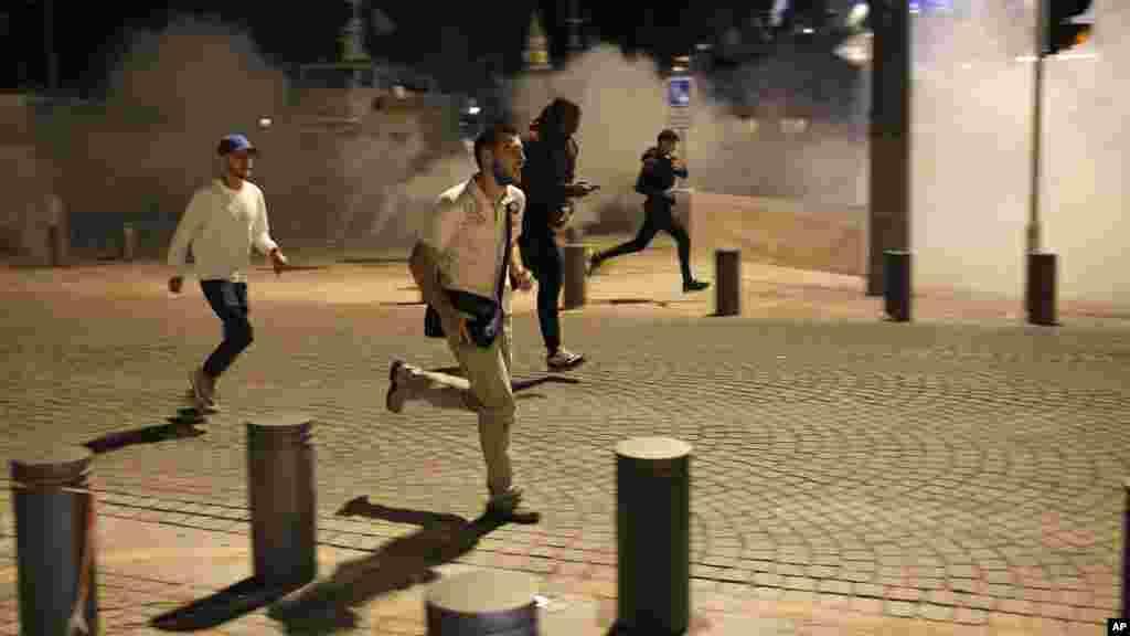 Des fans courent dans les rues de Marseille, après que la police a tiré des gaz lacrymogènes, le 11 juin 2016.