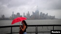 A woman shields herself from rain and wind produced by Tropical Storm Fay with an umbrella as she walks along the Hudson River in front of the skyline of New York City, July 10, 2020.