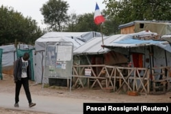"A migrant walks past a shelter with a French flag in the southern area of the camp called the ""Jungle"" in Calais, France, Sept. 26, 2016."