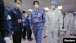 日本首相安倍晉三12月29日身穿防護衣和防護面具視察了東京電力公司所屬的福島核電站。