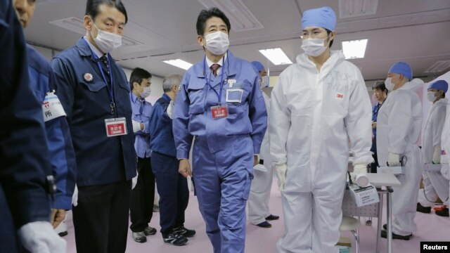 Japan's new prime minister, Shinzo Abe (C), tours the emergency operations center of the crippled Fukushima nuclear power plant December 29, 2012.