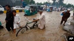 Cư dân lột qua con đường bị ngập lụt vì mưa mùa tại Peshawar, Pakistan, ngày 5/8/2013.