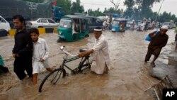 Kendaraan dan warga Peshawar, Pakistan melintasi jalanan yang banjir akibat hujan lebat yang mengguyur wilayah ini, Sabtu (3/8). Hujan lebat selama tiga hari belakangan ini di berbagai wilayah di Pakistan dilaporkan telah menewaskan sedikitnya 53 orang.