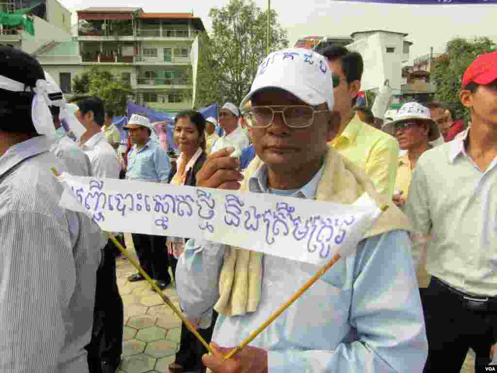 """A protester holds a sign reading """"The new voters' registration will be accurate."""" (Heng Reaksmey/VOA Khmer)"""