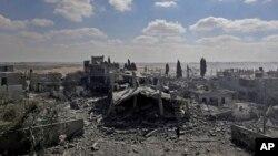 Gazze Şeridi'nin kuzeyindeki Beyt Hanun'da enkaz haline gelen evlerini inceleyen Filistinliler