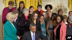 FILE - Then-President Barack Obama signs executive actions, with pending Senate legislation, aimed at closing a compensation gender gap that favors men, during an event marking Equal Pay Day in Washington, April 8, 2014. On April 9, in a straight-party-line vote, the Paycheck Fairness Act was blocked by a Republican filibuster in the Senate.
