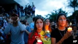 Anti-government demonstrators hold candles during a vigil in honor of those who have been killed during clashes between security forces and demonstrators in Caracas, Venezuela, Monday, July 31, 2017.
