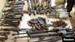 Weapons and ammunition seized from suspected members of Islamist rebel force Boko Haram are displayed during a military patrol in Hausari village, near Maiduguri, Nigeria, June 5, 2013.