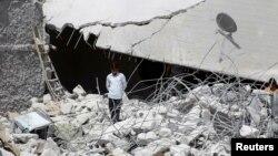 Un homme marche au milieu des gravats d'un immeuble détruit ; les jihadistes pointent du doigt les frappes aériennes de l'armée de l'air américaine à Kedrian, dans la province d'Idlib, le 24 septembre 2014, Syrie.