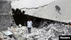 Cư dân đứng trên các mảnh vỡ của tòa nhà trong tỉnh Idlib ở tây bắc Syria bị hư hại sau những cuộc không kích của liên minh.