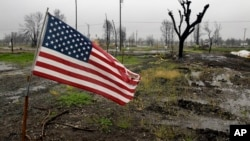 A U.S. flag is seen on wildfire-ravaged property as rain comes down in the Coffey Park area, April 6, 2018, in Santa Rosa, Calif. A fierce Northern California storm Friday threatened mudslides in wildfire-ravaged wine country.