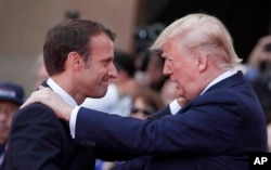 French President Emmanuel Macron (L) meets U.S President Donald Trump during a ceremony to mark the 75th anniversary of D-Day at the Normandy American Cemetery in Colleville-sur-Mer, Normandy, France, June 6, 2019.