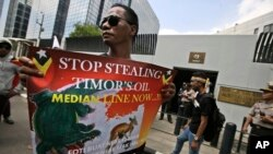 FILE - In this March 24, 2016 file photo, a protester holds a poster during a rally outside the Australian Embassy in Jakarta, Indonesia, as dozens of people show their support to East Timor in the dispute over oil and gas revenue-sharing between the two