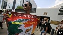 Foto yang diambil pada 24 Maret 2016 menunjukkan seorang demonstran memegang poster saat berdemo di depan Kedutaan Australia di Jakarta, Indonesia, menunjukkan dukungan terhadap Timor Leste dalam masalah pertikaian pembagian kekayaan minyak dan mineral Laut Timor.