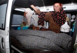 A women mourns over the body Farzana Parveen, who was killed by family members, in an ambulance outside of a morgue in Lahore, May 27, 2014.