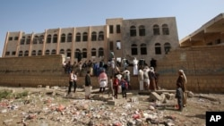People gather at a school damaged by Saudi-led airstrikes in Sanaa, Yemen, July 20, 2015.