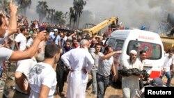 Seorang Muslim Sunni berlari membawa potongan tubuh yang terbakar sesudah terjadi ledakan bom di luar masjid di Tripoli, Lebanon (23/8)