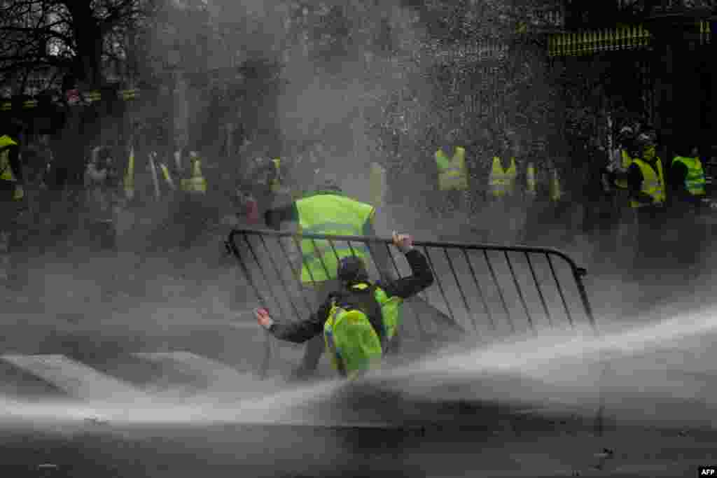 Anti-riot police use a water cannon during clashes with 'yellow vest' (Gilet Jaune) protesters during a demonstration, near major EU buildings in Brussels, Belgium.