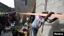 Yon imigran ayisyen kap pote planch pou al bati yon kay nan yon katye sou fwontyè Meksik ki rele Tijuana a. Foto 25 fevriye 2017.