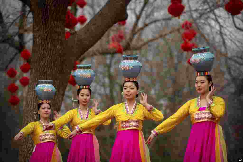 Dancers in traditional ethnic clothing perform at a temple fair at Longtan Park in Beijing, China. Chinese people are celebrating the second day of the Lunar New Year, the Year of the Pig on the Chinese zodiac.