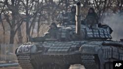 ພວກກະບົດທີ່ໜຸນຫຼັງໂດຍຣັດເຊຍ ຂີ່ລົດຖັງ ຢູ່ນອກເມືອງ Luhansk ຂອງຢູເຄຣນ, ວັນທີ 21 ກຸມພາ 2015.