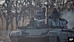 Pemberontak pro-Rusia mengendarai tank di luar Luhansk, Ukraina, 21 Februari 2015.