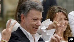 Colombia's President Juan Manuel Santos makes the victory sign after voting in a referendum to decide whether or not to support the peace deal he signed with rebels of the Revolutionary Armed Forces of Colombia, FARC, in Bogota, Colombia, Oct. 2, 2016.