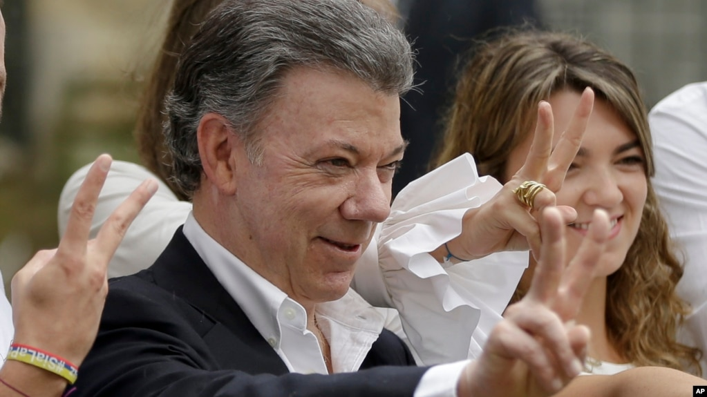 FILE - Colombia's President Juan Manuel Santos makes the victory sign after voting in a referendum to decide whether or not to support the peace deal he signed with rebels of the Revolutionary Armed Forces of Colombia, FARC, in Bogota, Colombia, Oct. 2, 2016.