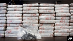 FILE - A firearm and 154 pounds of heroin worth at least $50 million are displayed by the Drug Enforcement Administration in New York, May 19, 2015. An annual DEA survey released Nov. 4, 2015, says heroin and drug overdoses have reached epidemic levels in the U.S.