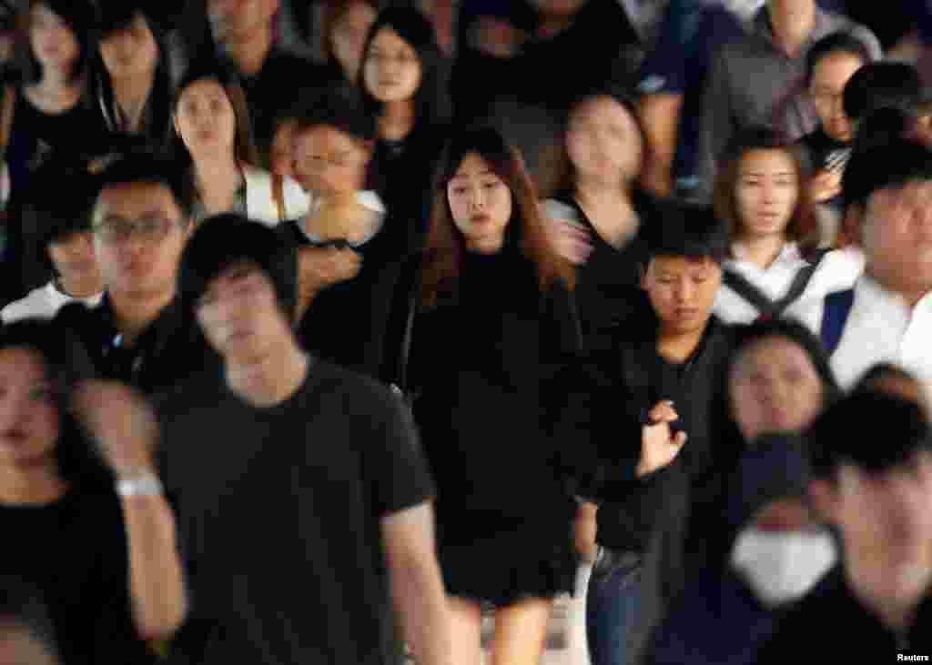 Para penumpang Thailand memakai pakaian hitam-hitam untuk berduka cita atas meninggalnya Raja Bhumibol Adulyadej di sebuah stasiun kereta di Bangkok.