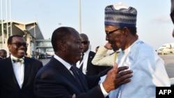 Le président nigérian Muhammadu Buhari, à droite, échange une accolade avec son homologue ivoirien, Alassane Ouattara, à son arrivée à l'aéroport Félix Houphouët-Boigny, à Abidjan, Côte d'Ivoire, 28 novembre 2017.