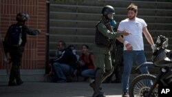 Un manifestante antigubernamental es detenido por las autoridades en Caracas.