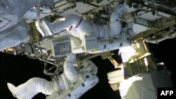 Dua astronot dari stasiun antariksa NASA, Chris Cassidy (atas) dan Tom Marshburn bekerja memperbaiki kebocoran di stasiun tersebut (11/5). (AFP/NASA)