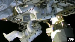 In this still image taken from NASA TV, International Space Station astronauts Chris Cassidy (top) and Tom Marshburn work on repairs to the ISS on May 11, 2013.