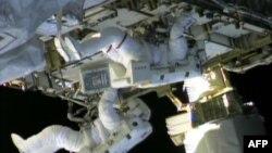 ພາບຈາກໂທລະພາບຂອງອົງການ NASA TV ນັກບິນ ອະວະກາດ Chris Cassidy (ຂ້າງເທິງ)ແລະ Tom Marshburn ເພື່ອສ້ອມແປງການຮົ່ວໄຫລ ຂອງສານເຮັດຄວາມເຢັນ ammonia ຢູ່ນອກສະຖານີອະວະກາດສາກົນ ໃນວັນເສົາ ທີ 11 ພຶດສະພາ, 2013.
