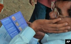 An unidentified man looks on as he holds a pamphlet on the four former Khmer Rouge top leaders—Nuon Chea, Khieu Samphan, Ieng Sary and Ieng Thirith.