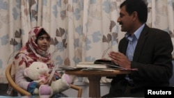 Em Malala nói chuyện với bố của mình tại bệnh viện Nữ hoàng Elizabeth, Birmingham.