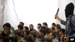 FILE - This undated photo posted Aug. 27, 2014, by the Raqqa Media Center of the Islamic State group shows an IS fighter, armed with a knife and an automatic weapon, next to captured Syrian army soldiers and officers after the battle for the Tabqa air base in Raqqa, Syria.