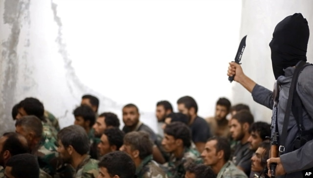 FILE - This undated file photo posted on Wednesday, Aug. 27, 2014 by the Raqqa Media Center of the Islamic State group, a Syrian opposition group, which has been verified and is consistent with other AP reporting, shows a fighter from the Islamic State group with Syrian prisoners.