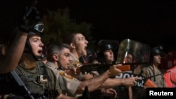 Security forces charge demonstrators after being hit by water bottles during a protest against the shooting of unarmed black teen Michael Brown in Ferguson, Missouri Aug. 20, 2014.