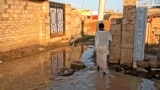A man walks through a flooded street in the al-Kalakla neighborhood of Sudan's capital, Khartoum, Sept. 7, 2021.