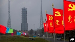 Flags with the logo of the Communist Party of China fly in the breeze near a launch pad at the Wenchang Space Launch Site in Wenchang in southern China's Hainan province, Monday, Nov. 23, 2020.
